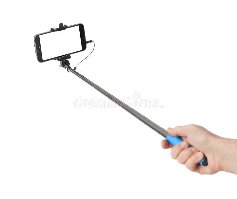 Main et smartphone avec le bâton de selfie images libres de droits