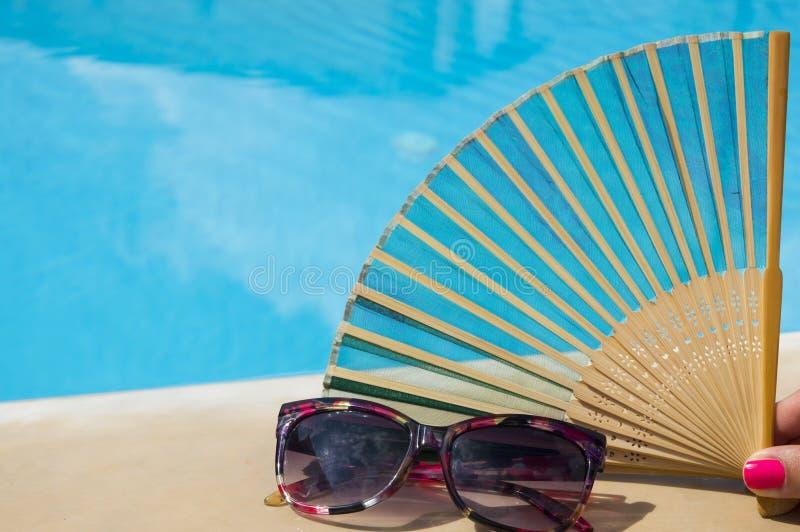 Main-fan dans la main de filles à côté des lunettes de soleil avec de l'eau bleu clair photographie stock