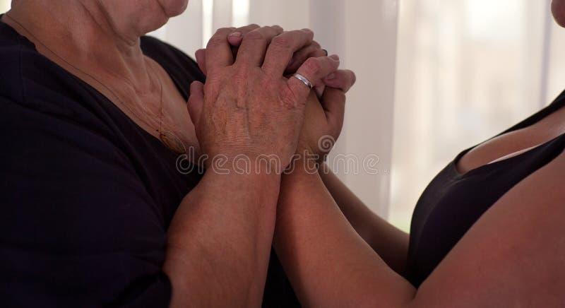 Main femelle émouvante de jeunes mains femelles vieille - prendre soin de photos libres de droits