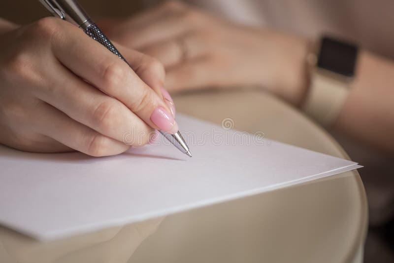 Main femelle avec l'écriture de stylo photos stock