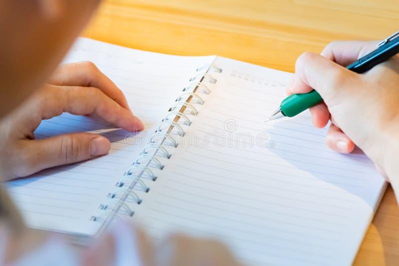 main femelle avec l'?criture de crayon sur le carnet au caf? femme travaillant ? la main l'inscription sur le papier de lettre su photographie stock
