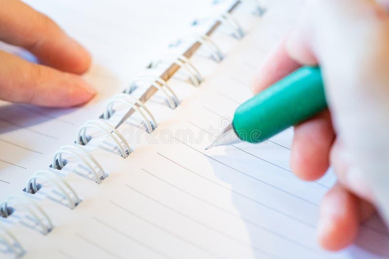 main femelle avec l'?criture de crayon sur le carnet au caf? femme travaillant ? la main l'inscription sur le papier de lettre su photo stock