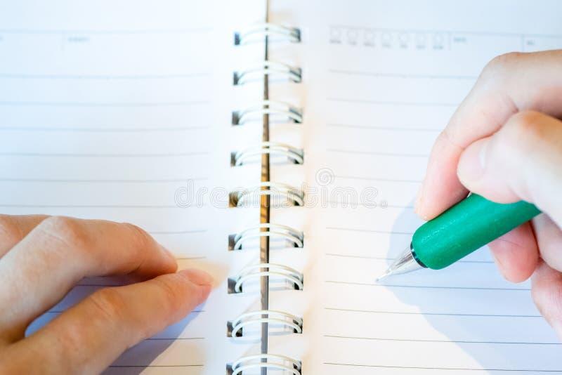 main femelle avec l'?criture de crayon sur le carnet au caf? femme travaillant ? la main l'inscription sur le papier de lettre su photographie stock libre de droits