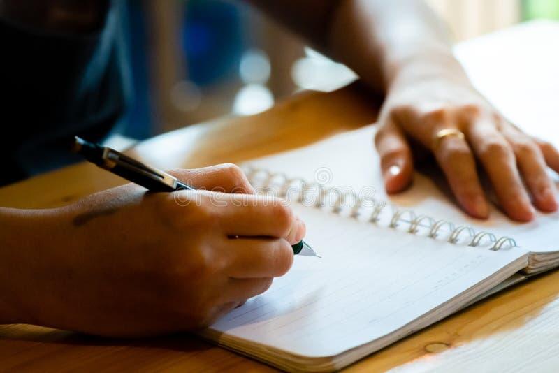 main femelle avec l'?criture de crayon sur le carnet au caf? femme travaillant ? la main l'inscription sur le papier de lettre su photo libre de droits
