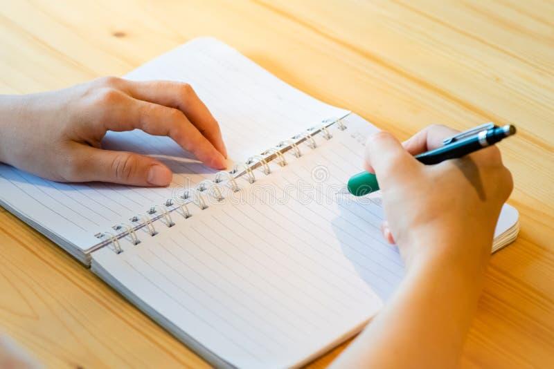 main femelle avec l'?criture de crayon sur le carnet au caf? femme travaillant ? la main l'inscription sur le papier de lettre su image stock
