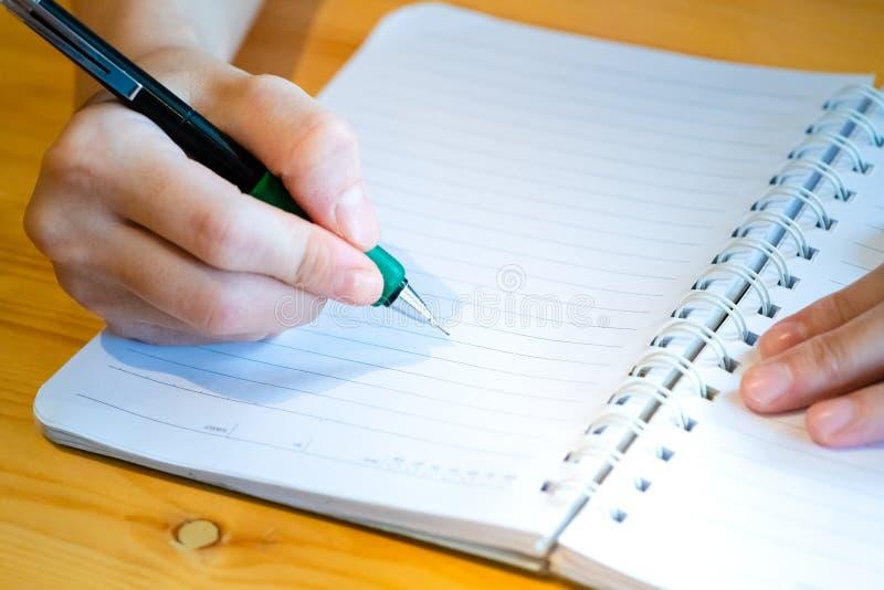 main femelle avec l'?criture de crayon sur le carnet au caf? femme travaillant ? la main l'inscription sur le papier de lettre su images libres de droits