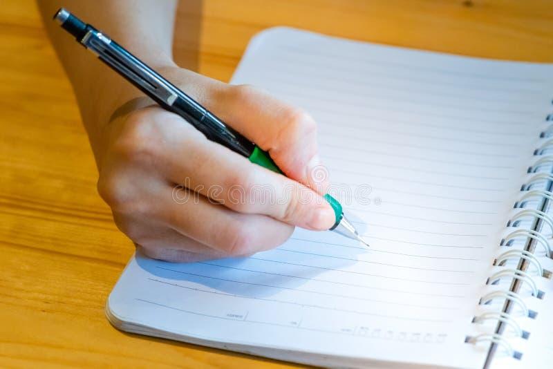 main femelle avec l'?criture de crayon sur le carnet au caf? femme travaillant ? la main l'inscription sur le papier de lettre su photos stock