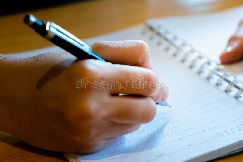 main femelle avec l'?criture de crayon sur le carnet au caf? femme travaillant ? la main l'inscription sur le papier de lettre su images stock