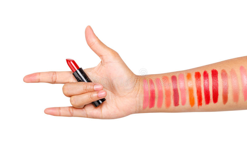 Main femelle avec la couleur rouge de rouge à lèvres rouge et le Li différent de essai images stock
