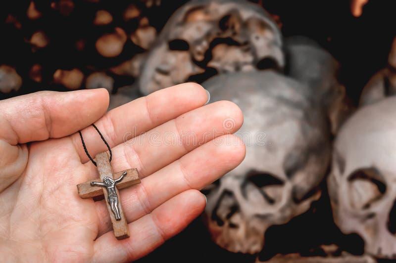 Main femelle avec la croix sur les cr?nes et le fond d'os photo stock