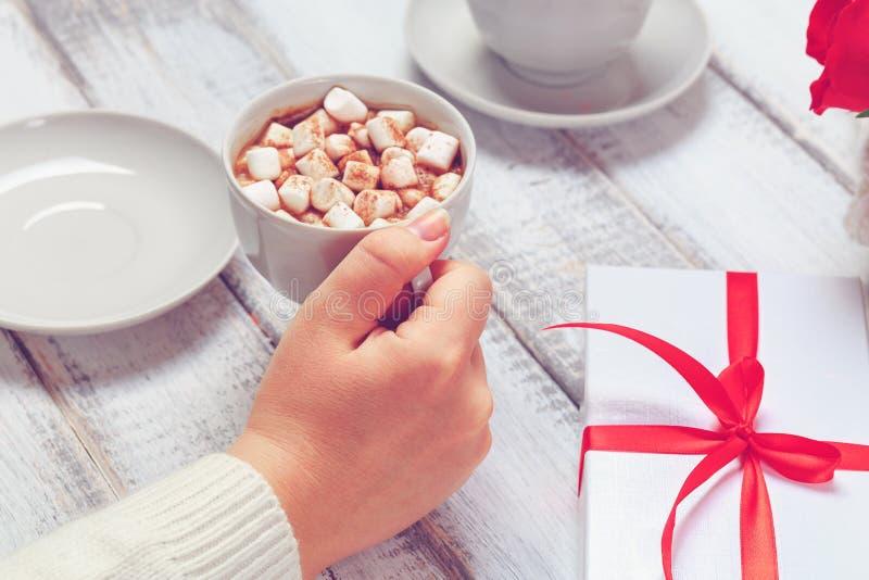 Main femelle avec la tasse de cacao chaud avec des guimauves, boîte-cadeau sur le bois blanc photo stock