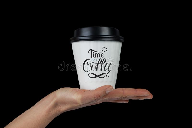 Main femelle avec la tasse de café blanc sur la paume photographie stock