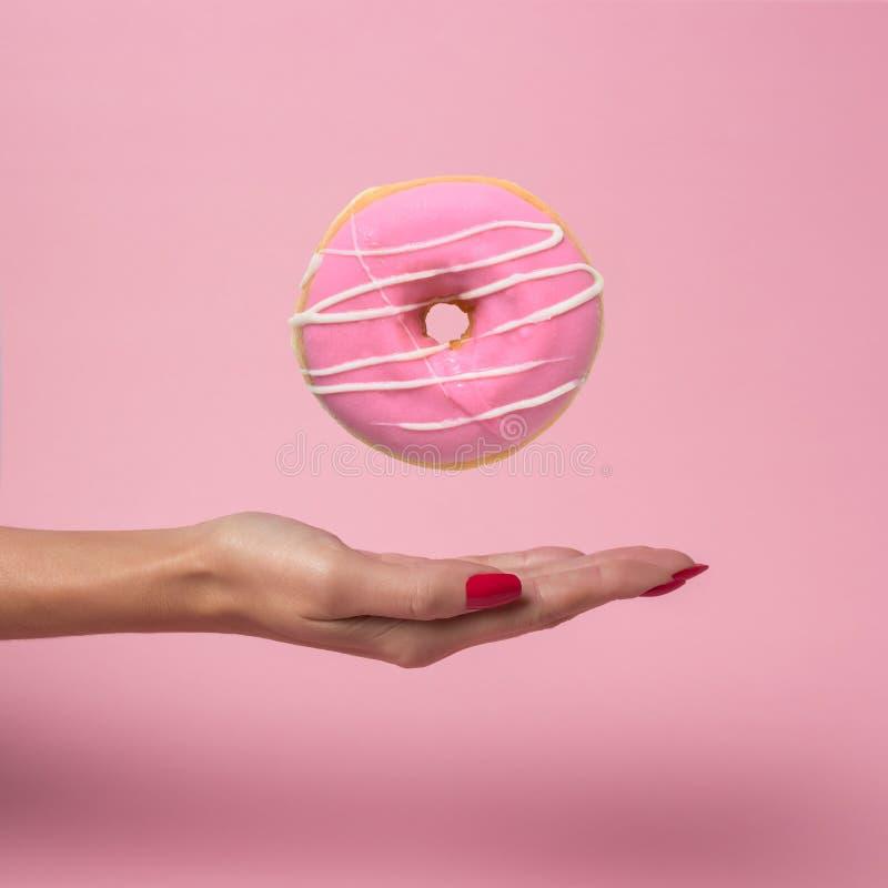 Main femelle avec le beignet délicieux de vol sur le fond rose photographie stock