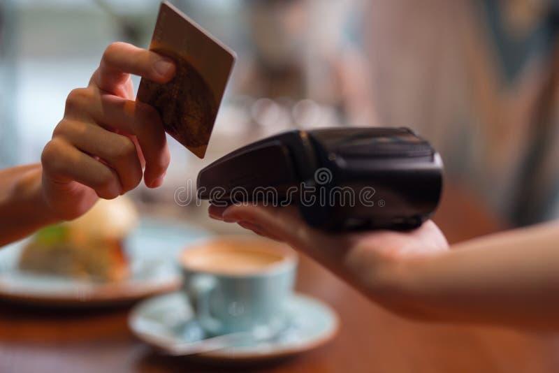 Main femelle avec le grand coup de carte de crédit par le terminal photos stock