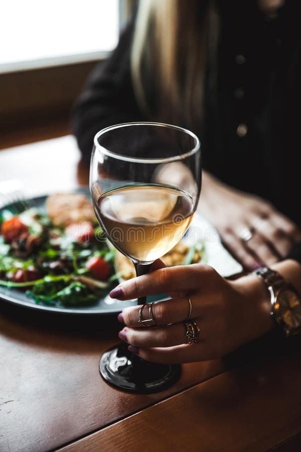 Main femelle avec le verre de vin et de nourriture à l'arrière-plan photographie stock