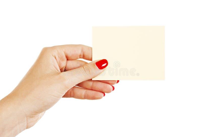 Main femelle avec les clous rouges tenant une carte vierge images libres de droits
