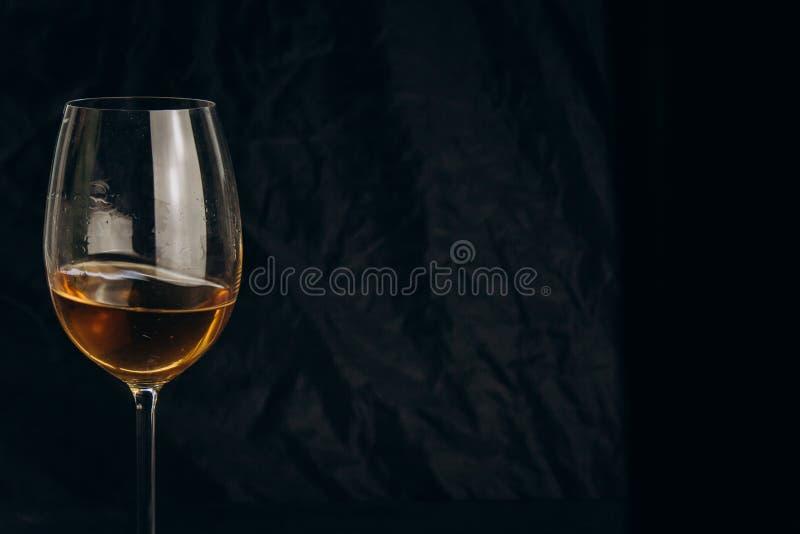 Main femelle cultivée tenant un verre de vin blanc sur un fond noir repos, vacances, partie plan rapproché de boisson alcoolisée photo stock