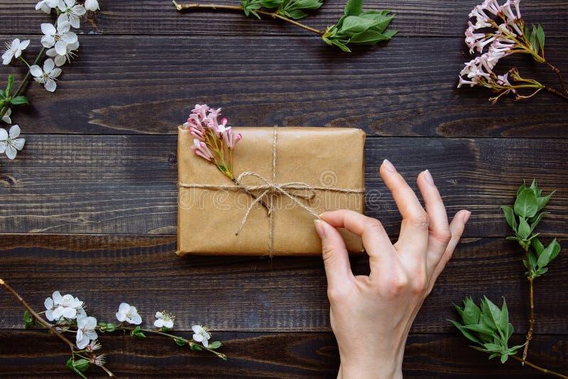 Main femelle déballant le boîte-cadeau enveloppé avec le papier et les fleurs de métier sur la vue supérieure en bois de table Ca image stock