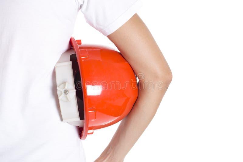Main femelle d'ingénieur tenant le casque rouge image libre de droits