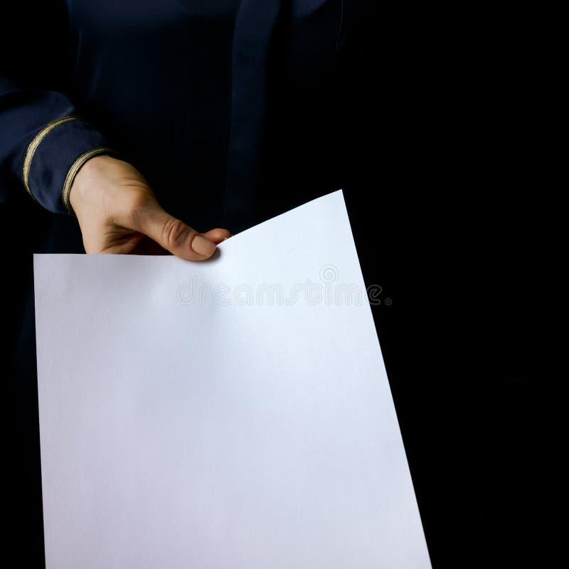 Main femelle d'isolement sur le fond noir donnant la feuille de papier image libre de droits
