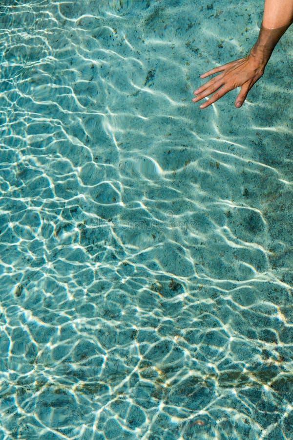 Main femelle dans l'eau froide d'une vieille fontaine image stock