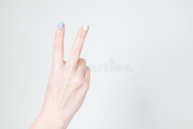 Main femelle dans le geste de victoire d'isolement sur le fond blanc photographie stock