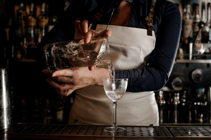 Main femelle de barman versant le cocktail frais dans un verre photographie stock libre de droits