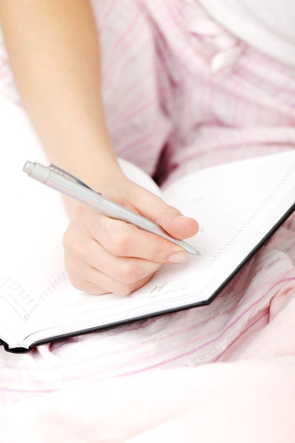 Main femelle effectuant des notes dans callendar images libres de droits