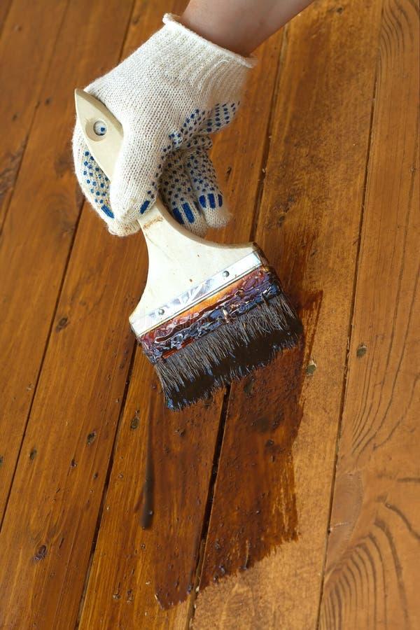 Main femelle en peintures le plancher en bois Photo de plan rapproché photographie stock