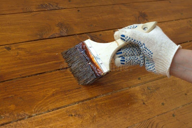 Main femelle en peintures le plancher en bois Photo de plan rapproché photos libres de droits