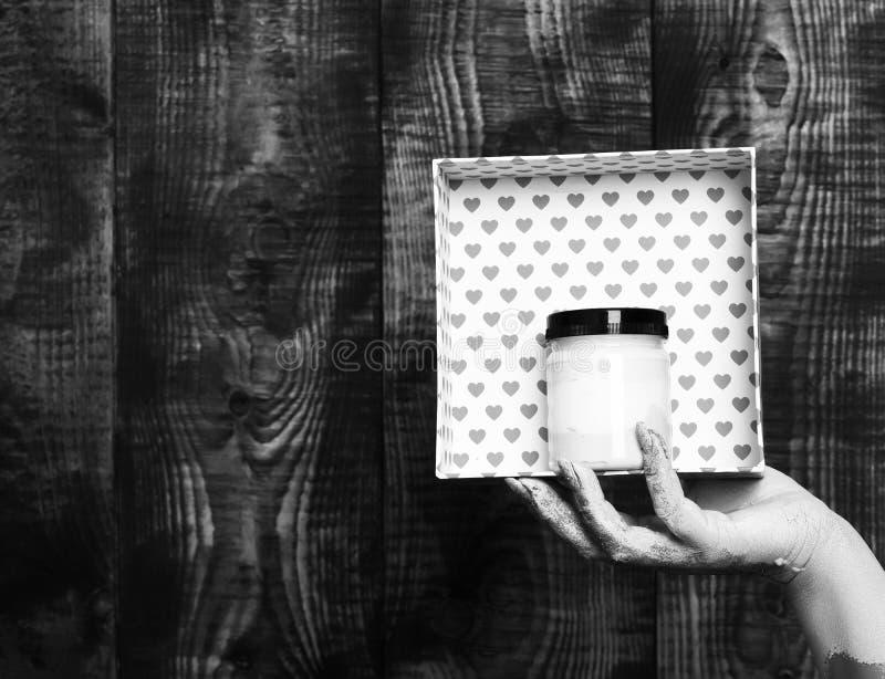 Main femelle enduite en peinture d'or ou glister tenant la boîte rose faite main de valentine de points de polka du présent sur l photos stock