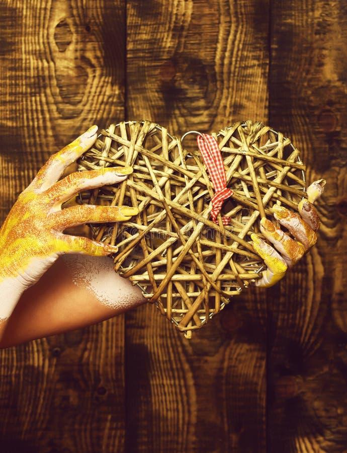 Main femelle enduite en peinture d'or ou glister tenant le coeur gris décoratif de valentine sur le backgroun brun de studio de v images libres de droits