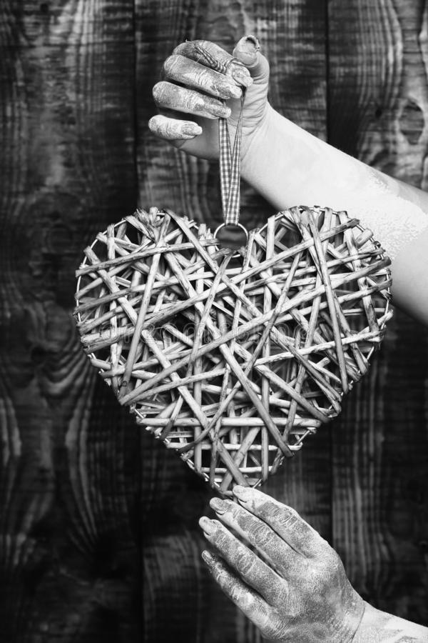 Main femelle enduite en peinture d'or ou glister tenant le coeur gris décoratif de valentine sur le backgroun brun de studio de v photographie stock