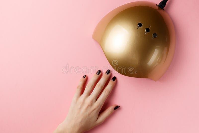 Main femelle et lumi?res UV de lampe pour des clous sur le fond rose Vue sup?rieure Configuration plate Copiez l'espace concept c photo stock