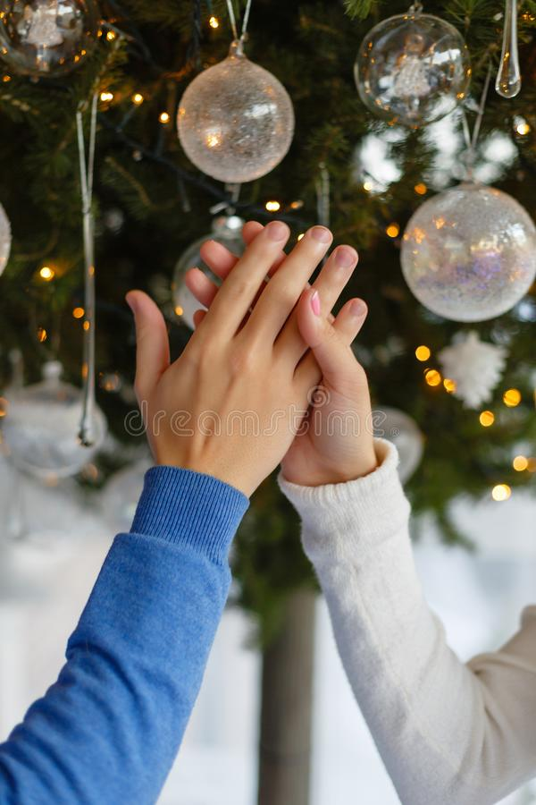 Main femelle et masculine sur le fond d'un arbre de Noël avec des jouets Jeunes couples tenant des mains ensemble dans Noël décor photographie stock