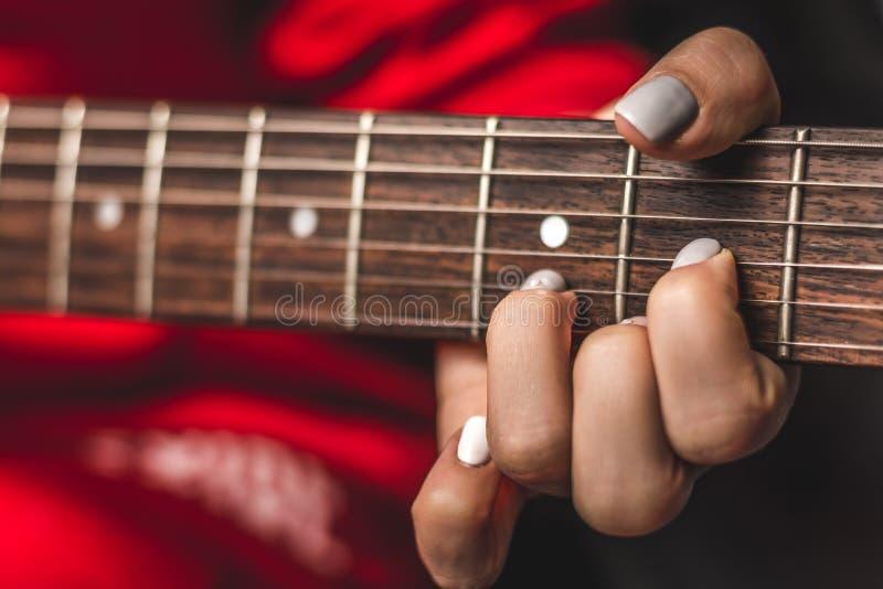 Main femelle jouant sur la guitare image stock