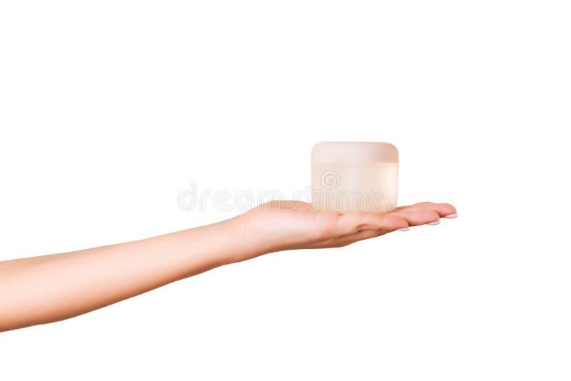 Main femelle jugeant la bouteille crème de lotion d'isolement La fille donnent à pot les produits cosmétiques sur le fond blanc images stock
