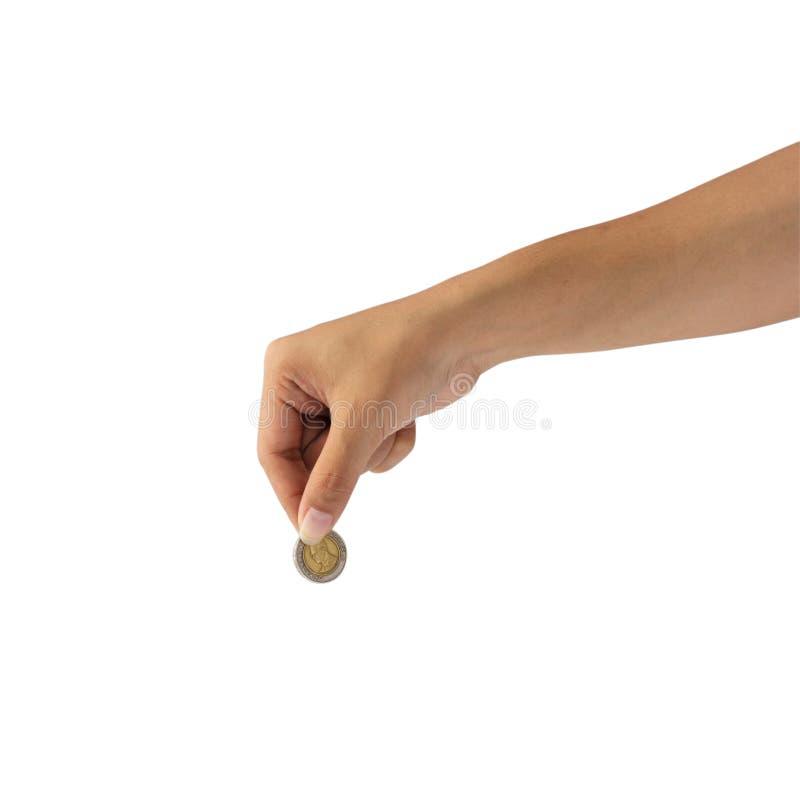 Main femelle jugeant la pièce de monnaie d'isolement sur le fond blanc avec le chemin de coupure photographie stock