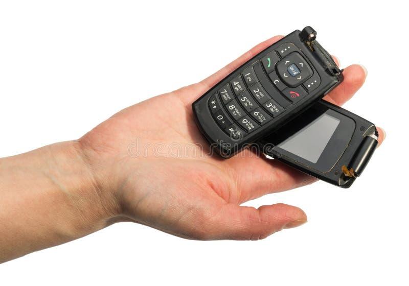 Main femelle jugeant le téléphone portable cassé d'isolement sur le backgr blanc image stock