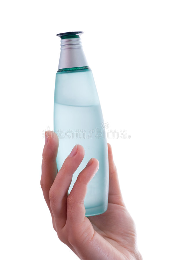 Main femelle jugeant une bouteille de parfum d'isolement photo stock