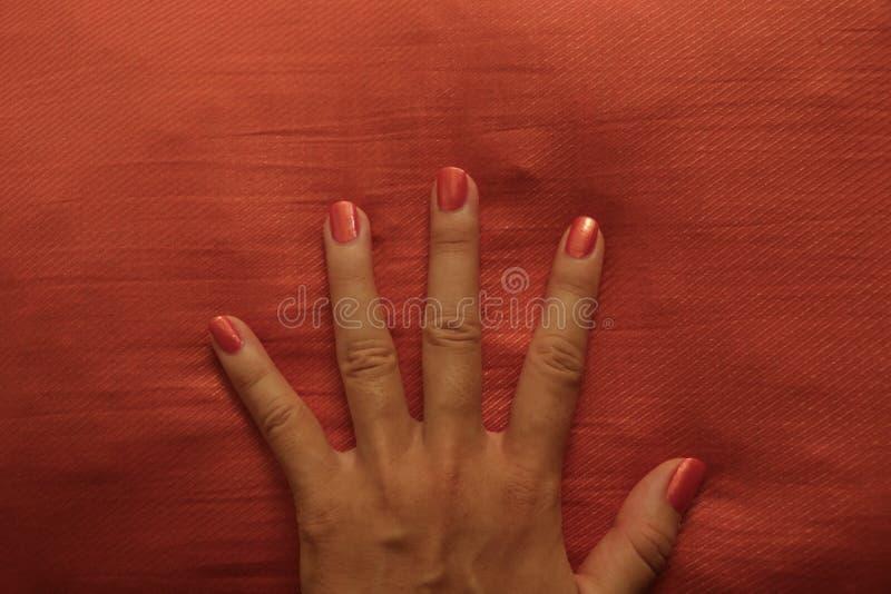 Main femelle Manicured avec le coussin orange lumineux d'orange de Gabbing de vernis à ongles photo libre de droits