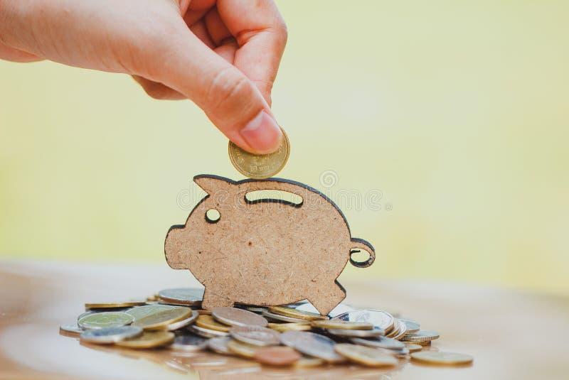 Main femelle mettant la pièce de monnaie et la pile de pièces de monnaie dans le concept de l'épargne et de l'élevage d'argent ou images stock