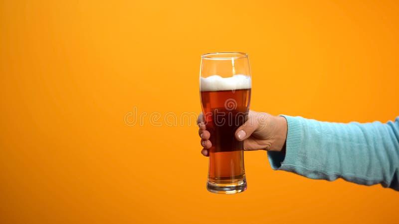 Main femelle montrant le verre de bi?re sur le fond jaune, clients de invitation au bar images stock