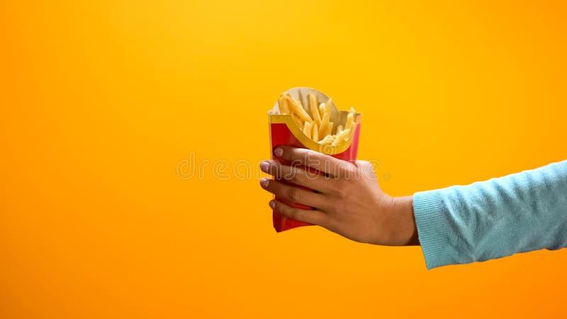 Main femelle montrant les pommes frites, clients de invitation au restaurant d'aliments de pr?paration rapide photo stock