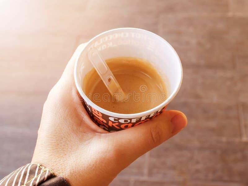 Main femelle ou main de femme tenant une tasse de carton avec du café chaud dehors photographie stock