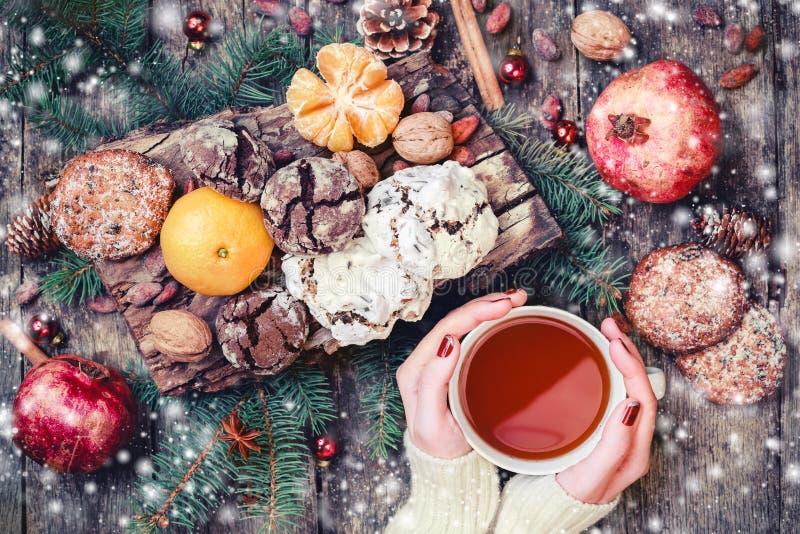 Main femelle par tasse de thé Biscuits chocolat, thé, grenade, mandarines, écrous, graines de Noël de cacao sur le fond neigeux e photo stock