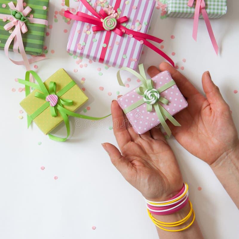 Main femelle retenant un cadeau Cadeau emballé en papier rose coloré image stock