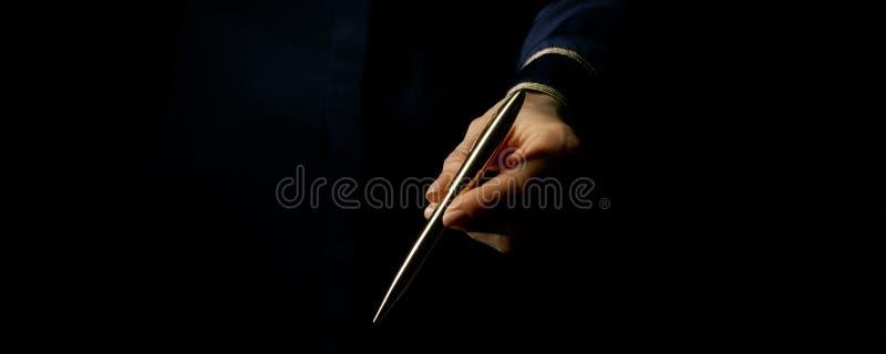 Main femelle sur le stylo donnant noir photo libre de droits