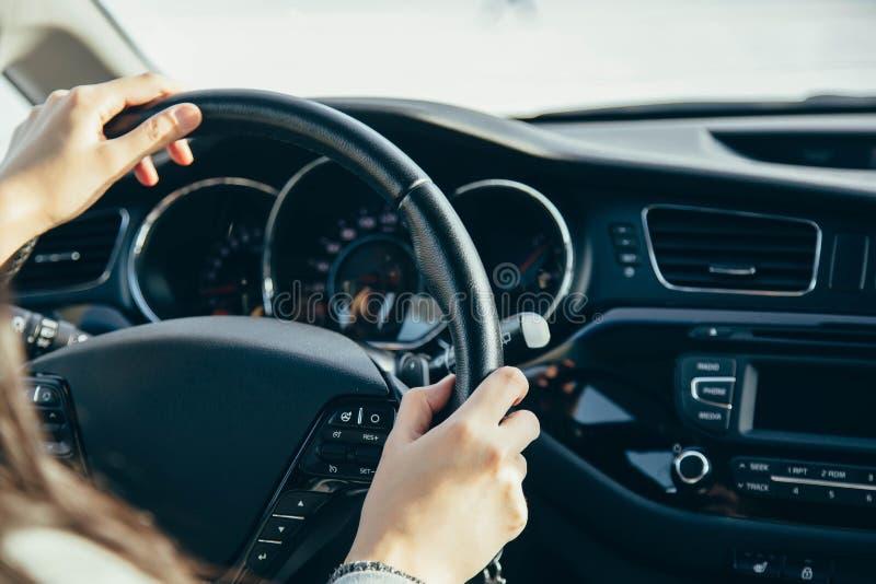 Main femelle sur les roues d'entraînement Entraînement d'un plan rapproché moderne de volant et de main de voiture photographie stock libre de droits