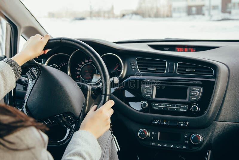 Main femelle sur les roues d'entraînement Entraînement d'un plan rapproché moderne de volant et de main de voiture images stock